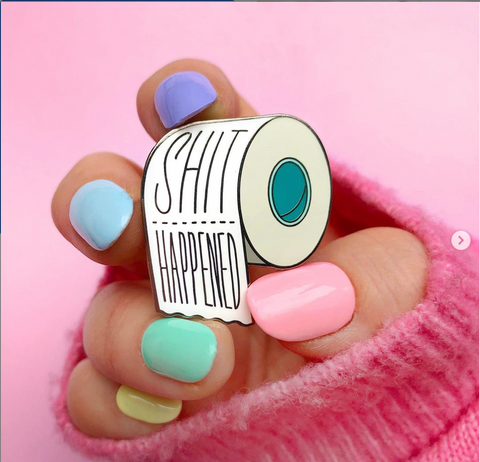 """A hand holding an enamel pin that says """"Shit Happens"""" and pastel coloured nails."""