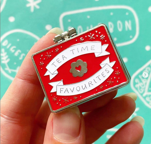 A hand holding a biscuit enamel pin.