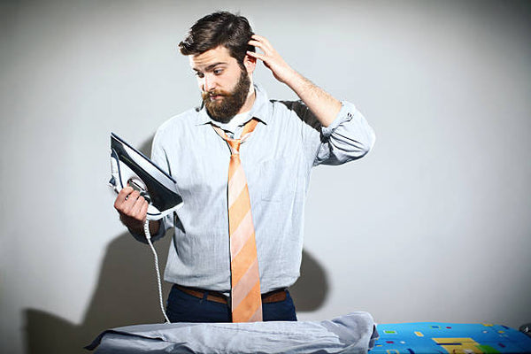Confused man ironing shirt suit and tie