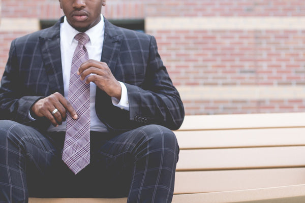 Suited Man Sitting Down Holding His Tie