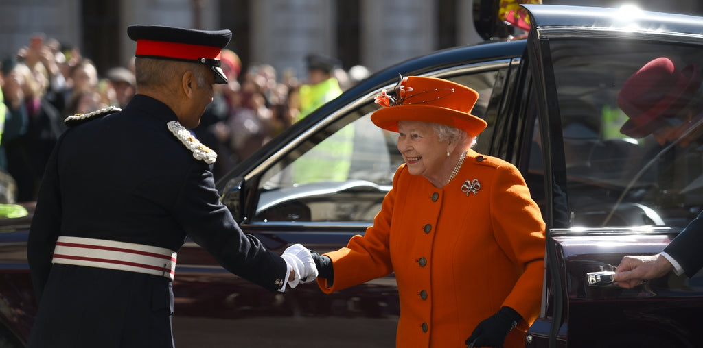 The Queen visits the royal academy in orange coordinated outfit.