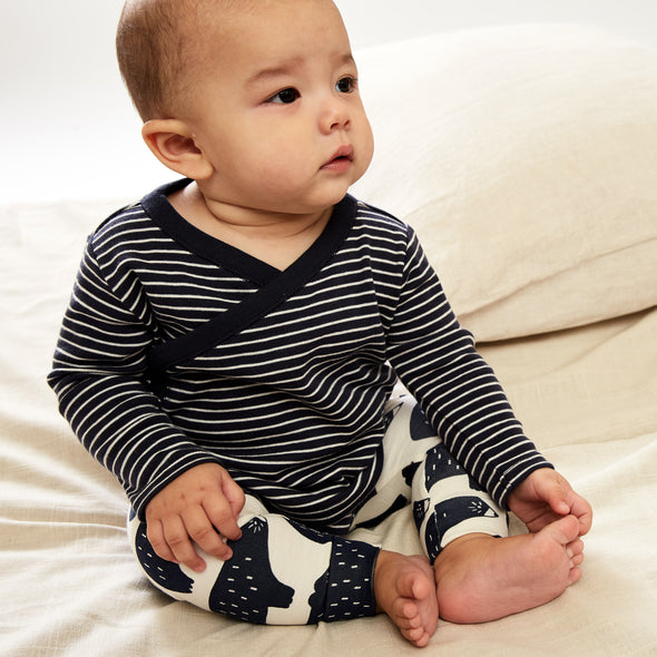 Baby boy sitting up wearing a wrap style top with navy and white stripes and pants with bears printed on them. Outfit by Tea Collection.