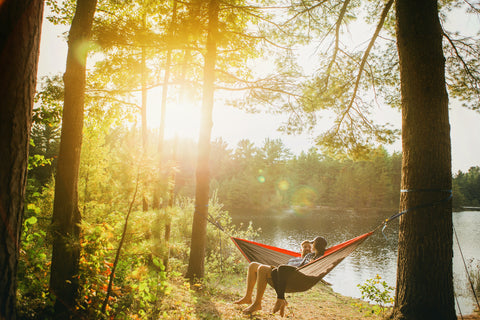 two people sitting in a hammock tied to trees in the woods