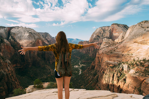 picture of a person standing at the edge of a cliff looking over mountains
