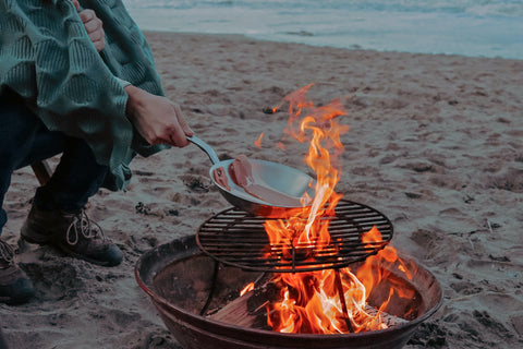 picture of a person cooking with a pan over a campfire