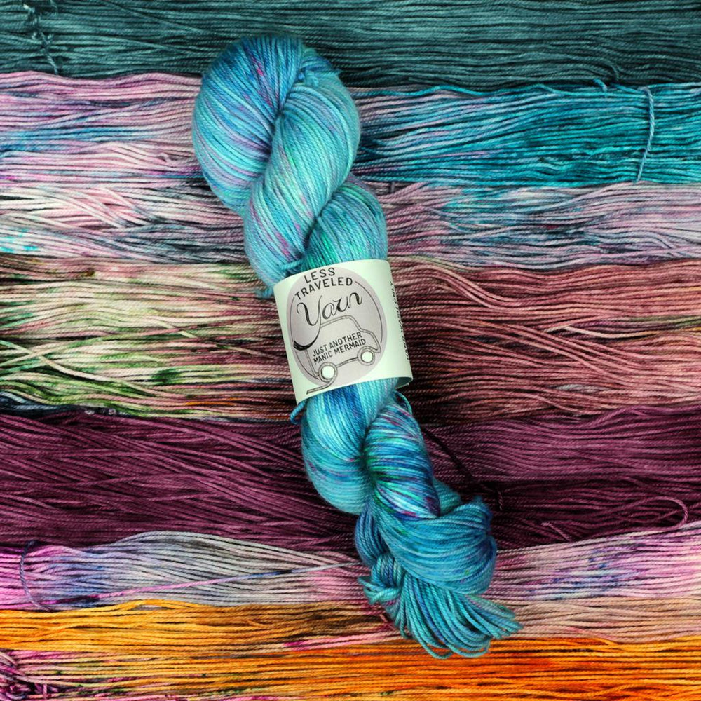 blue skein of yarn on background of several other colors of yarn