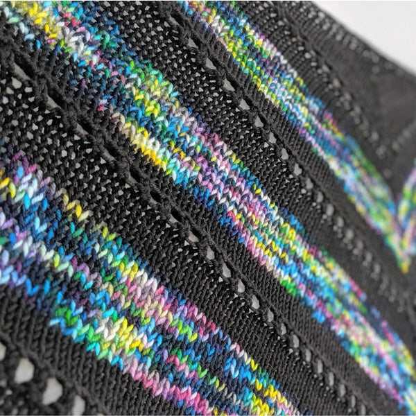 Closeup of triangular hand knit kerchief shawlette in black and a multi-color fluorescent yarn