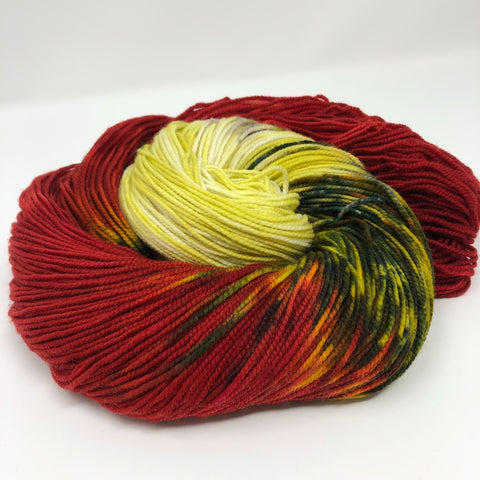 skein of Knitted Wit Victory Sock in Bloody Mary color - red and yellow and green yarn