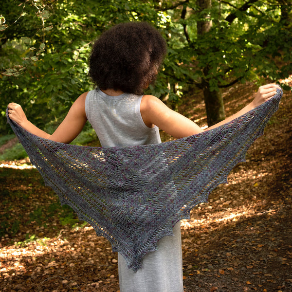 woman outside wearing gray triangular crochet shawl