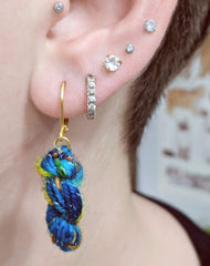 mini yarn skein earrings on an ear with multiple piercings above