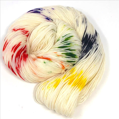 white yarn with spots of red yellow green blue and purple