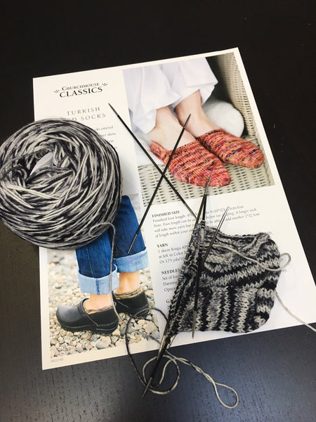 double pointed needles knitting a sock sitting on a pattern