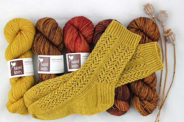 handknit yellow sock on top of skeins of red, orange, and yellow yarn