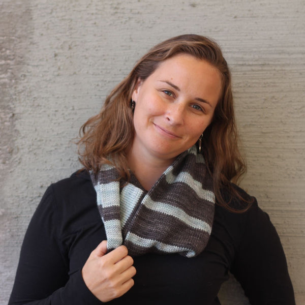 woman wearing gray and pale aqua striped handknit cowl and black sweater