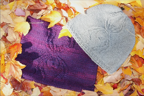 purple handknit cowl and grey handknit hat on top of fall leaves