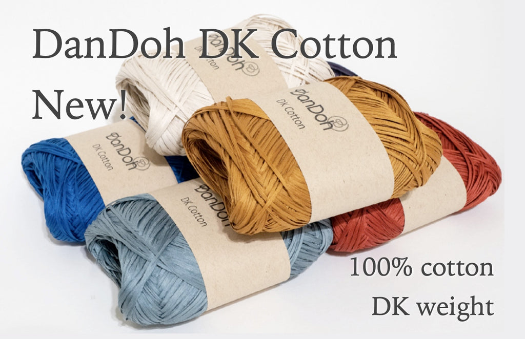 brightly colored red, orange, turquoise, blue, and natural skeins of cotton tape yarn in kraft paper wrappers on a white background with text overlay: DanDoh DK Cotton New! 100% cotton, DK weight