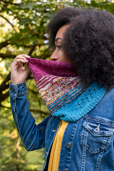 woman outside wearing denim jacket and pink and blue knit cowl