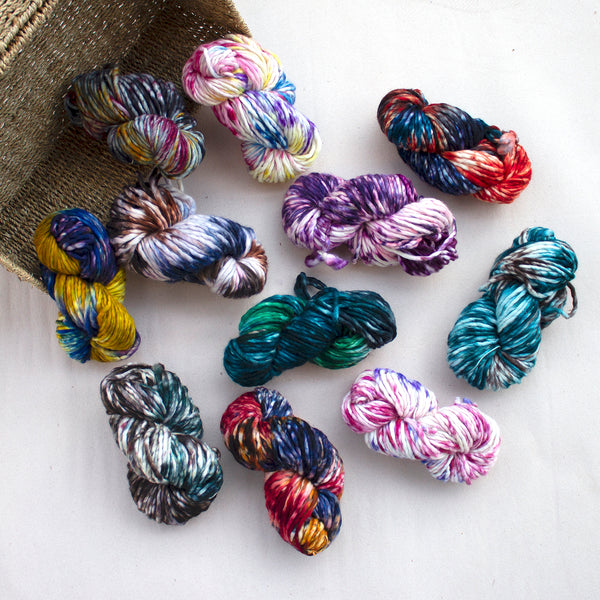 Skeins of brightly multi-color yarn spilling from a basket