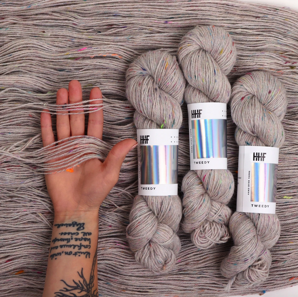 three skeins of natural/gray tweedy yarn atop a background of same yarn along with tattoed arm/hand for scale