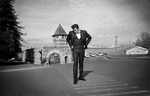 Johnny Cash standing outside the gates at Folsom Prison
