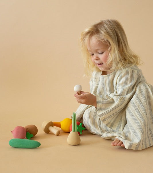Girl playing with Wooden Vegetables toy Set