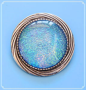 The Neptune brooch is predominately a bright, light blue however it is iridescent and has purple and green through it when the angle of view or the angle of illumination changes.