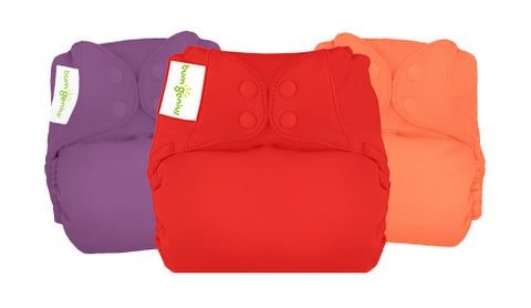 Image of three solid color cloth diapers, one purple, one red, one orange