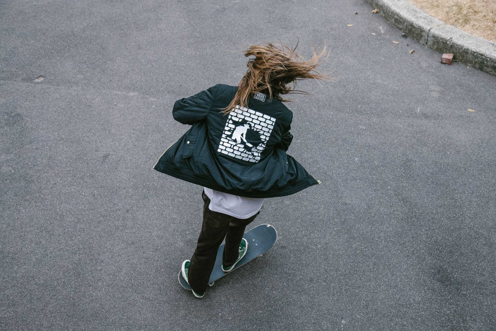 "skater riding in the street with the vans x passport bomber jackter with ""digging man"" print in the back"