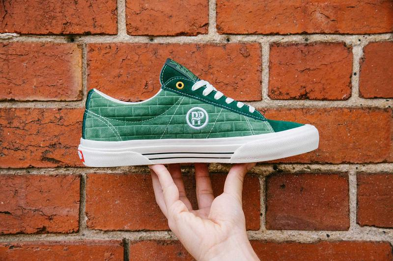 hand holding a green vans shoes, white sole, brick wall ,