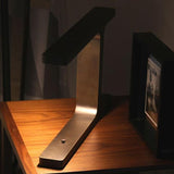 Narrow architectural table lamp in satin bronze with LED illumination