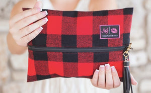 The Fireside Makeup Junkie Bag is a red and black flannel exterior with a soft wipeable interior. Seen on Shark Tank!
