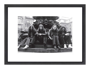 A print of all the Black Sabbath members sitting around a fountain in a plaza.