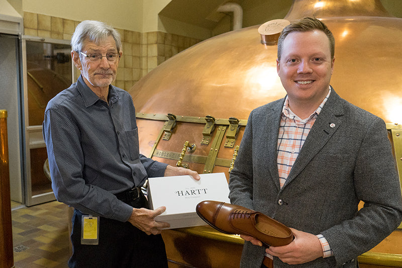 Owner of Moosehead, Derek Oland (left) holds a box of Hartt Shoes with Hartt CEO, Andrew Bedford.