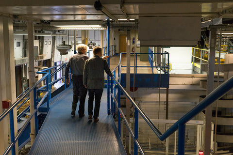 Owner of Moosehead Breweries, Derek Oland and Hartt Shoe Company CEO Andrew Bedford walk the on the catwalks in the Mooshead Brewery.