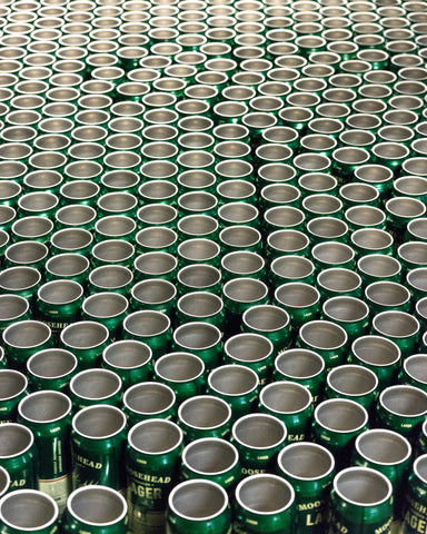 Untopped Moosehead cans roll down a conveyor belt in the Saint John Factory.