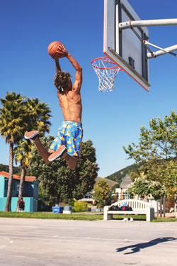man dunking a basketball outdoors