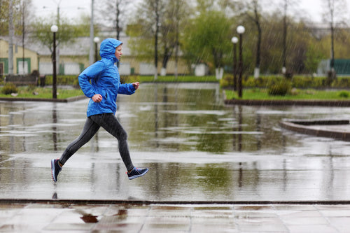 woman running in a park in rain