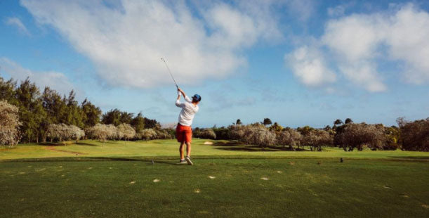 young man swinging golf club course