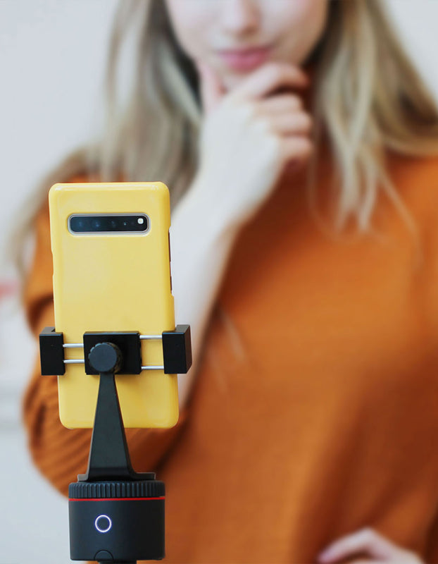 a yellow smartphone is mounted on smart mount which is tracking a woman