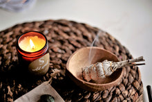 The Wild Pod home cleansing ritual kit with a Eucalyptus, Spearmint and Sparking Orange essential oil candle, sage stick, coconut shell sage bowl and crystal