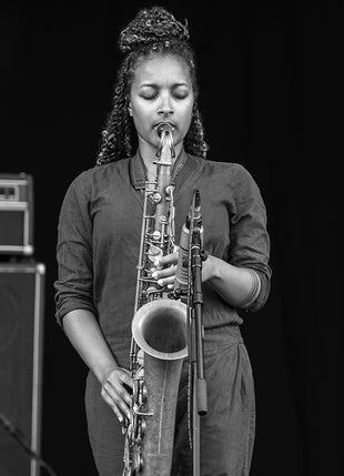 African woman playing saxophone live with microphone