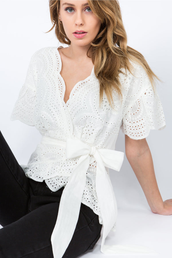 White lace faux wrap blouse with tie waist and scalloped hem