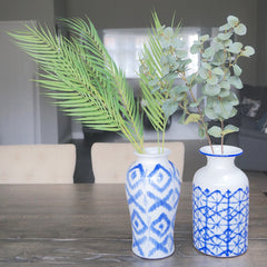 Fake palm leaves and eucalyptus leaves in large blue and white vases