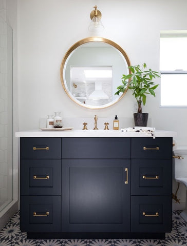 Dark navy blue vanity, large round brass mirror and brass hardware styled by Kirsten Marie Inc.