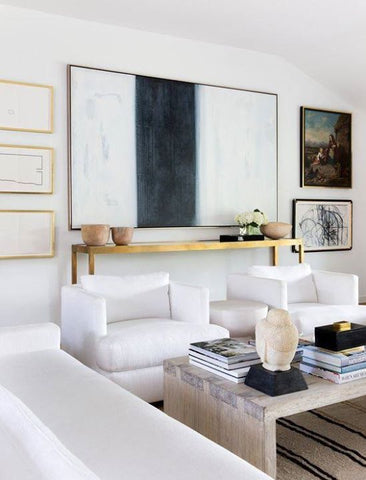 Living room with white sofas and armchairs, large abstract art print and brass furniture and frames