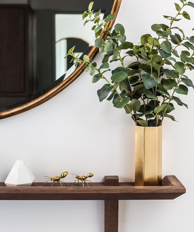 Polished brass vase with greenery, wooden console table, large round brass mirror styled by Gordon-Duff & Linton