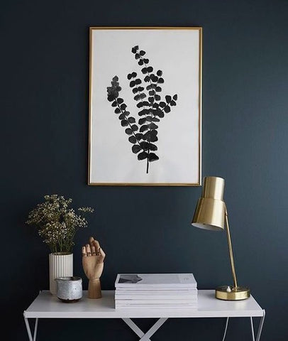 Dark navy walls, botanical print in brass frame, polish brass table lamp on white desk styled by Studio McGee