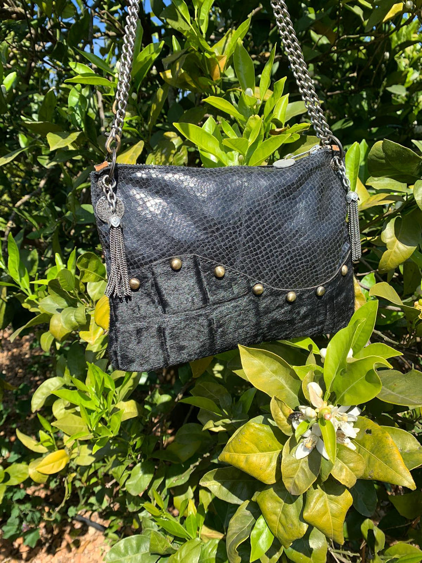 Our handmade leather black wavy crossbody handbag is 100% leather.  It is a small size bag and has a long adjustable metal chain. It is possible to wear it longer or shorter and it will be your best friend for nights out or everyday wear. It's a small size, elegant and practical.