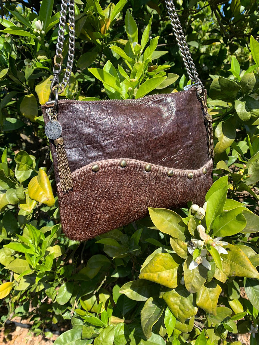 Our handmade leather brown wavy crossbody handbag is 100% leather.  It is a small size bag and has a long adjustable metal chain. It is possible to wear it longer or shorter and it will be your best friend for nights out or everyday wear. It's a small size, elegant and practical.