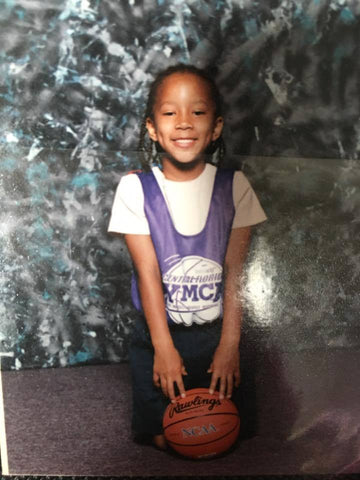 Brittany Crain around the age of 5 or 6 posing with a mini basketball.